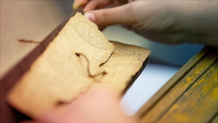Hand blättert durch ein altes Manuskript