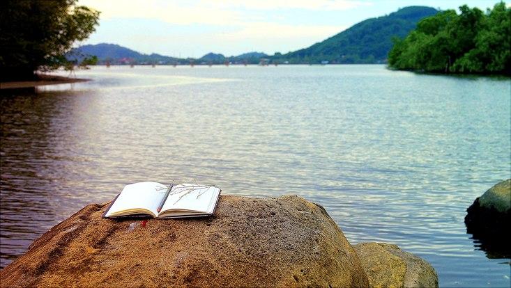 Geöffnetes Buch mit Stift auf Klippe im Hintergrund See und Berge