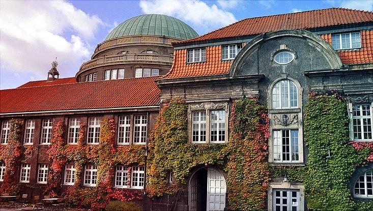 Seitenansicht des von buntem Efeu überwucherten Hauptgebäudes am Campus der Universität Hamburg