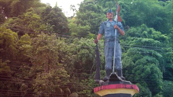 Militärstatue in West Papua mit Gewehr in der Hand, im Hintergrund dichter grüner Wald
