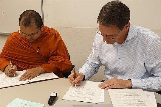 zwei personen am tisch unterzeichnen vereinbarung