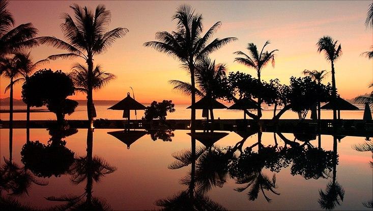 Sonnenuntergang auf Bali mit Palmen die sich im Wasser spiegeln