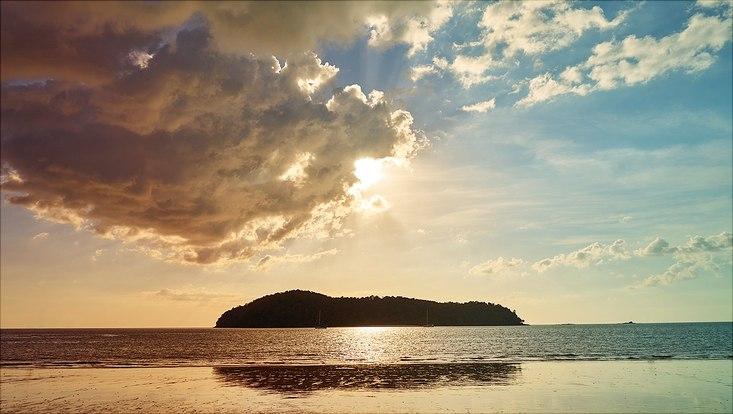 Insel im Meer und Sonne die hinter einer Wolke hervorscheint