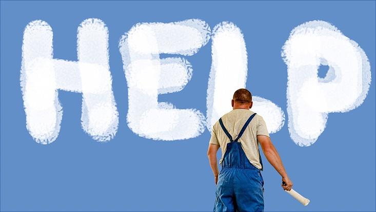 Mann schreibt HELP an eine blaue Wand