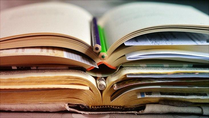 Aufgeschlagene Bücher gestapelt mit Stiften in der Mitte