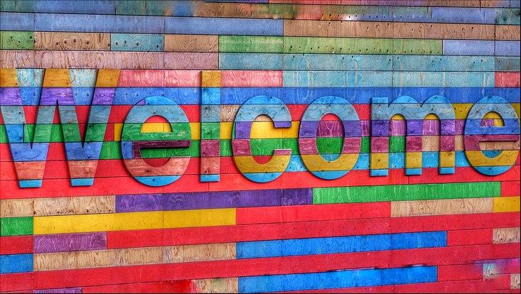"""Bunte Bretterwand mit dem Schriftzug """"Welcome"""""""