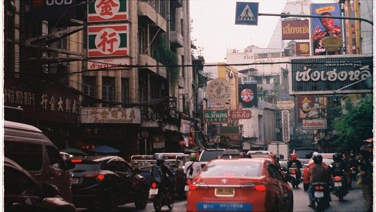 Straße mit Autos und thailändischen Rekalmetafeln