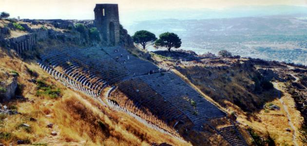 Überreste eines Halbrunds aus Zuschauerreihen mit Resten des oberen Umlaufgangs, allseits Graslandschaft mit Einzelbäumen, im Hintergrund Ebene