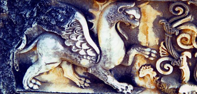 Tiefes Steinrelief mythischer Tierfigur mit nach rechts vorgestreckter Kralle, daneben Pflanzenornament