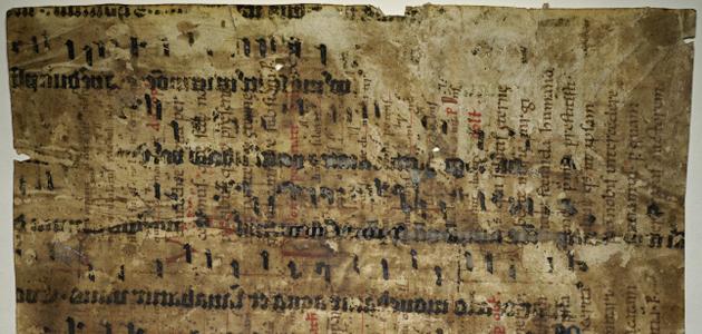 Ausschnitt aus Handschriftenseite, dicke spiegelverkehrte Textzeilen quer mit Neumen über dünnen, blasseren senkrechten Textzeilen mit nur als Punkten erkennbaren Neumen
