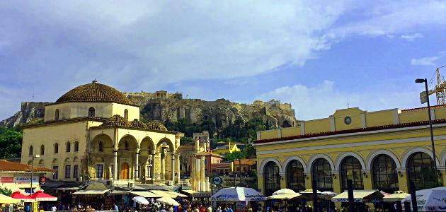Belebter Platz mit beschirmten Ständen, darunter Menschen (an Bildkante abgeschnitten) vor Kirche links und Metrostation mit Baukran rechts, im Hintergrund Hügel mit antiken Ruinen