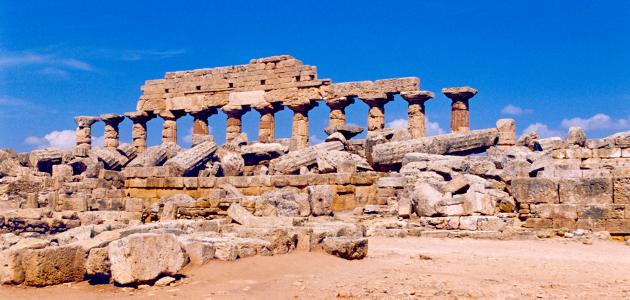 Trümmerfeld (gestürzte Säulen auf Mauer), dahinter Säulenreihe mit Resten von Überbau vor blauem Himmel