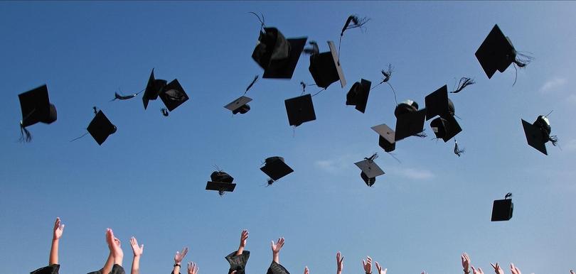 Hüte werden in die Luft geworfen nach Absolventenfeier