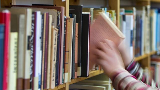 Buch wird aus Regal entnommen